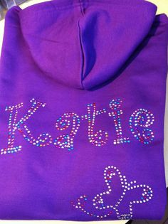 Katie hoodie, written in the bubbly Curlz font with a gorgeous, little butterfly. All done in the multi coloured bling to contrast against the deep purple hoodie. We can do this name and any other name in a variety of fonts/colours and apply it to a range of garments. For more info, please visit our website or give us a call!