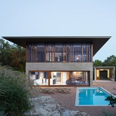 The flat roof of this house by Mell Lawrence Architects reaches well beyond the external walls, shading the glazed top floor from the harsh Texan sun.