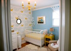 Sweet and simple yellow accents in this lovely blue #nursery.  #chandelier #wallpaper