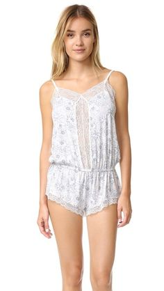 A floral Eberjey pajama romper with soft lace trim. Gathered elastic waistband. Adjustable shoulder straps.