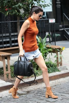 While out and about in NYC, Jenner channels the '70s in a burnt orange ribbed top, denim cut-off miniskirt, and lace-up suede boots.   - MarieClaire.com
