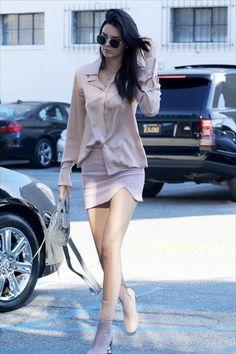 Kendall Jenner wears a light pink blouse, miniskirt, and matching Acne Studios boots