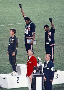 Gold medallist Tommie Smith (center) and bronze medalist John Carlos (right) showing the raised fist on the podium after the 200 m race at the 1968 Summer Olympics; both wear Olympic Project for Human Rights badges. Peter Norman (silver medalist, left) from Australia also wears an OPHR badge in solidarity to Smith and Carlos.