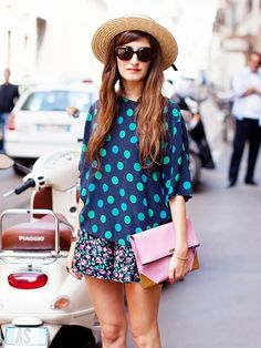 A polka dot t-shirt worn with a floral skirt, straw hat and pink clutch.