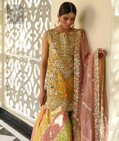 Amber shirt adorned with mainly light golden embellishment on neckline, hemline and side slits. Pink peach dupatta adorned with embellished border and stripes. Multiple color sharara adorned with border on hemline, stripes and motifs. Pakistani Mehndi Dress, Bridal Mehndi Dresses, Asian Wedding Dress, Pakistani Formal Dresses, Pakistani Wedding Outfits, Pakistani Bridal Dresses, Pakistani Wedding Dresses, Pakistani Dress Design, Bridal Outfits
