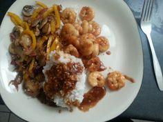Steamed rice and Shrimp with a orange sauce with yellow peppers, red onions and mushrooms  on the side.