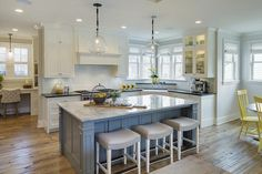 Yellow and gray kitchen features a pair of glass globe pendants hanging over a blue kitchen island topped with grey and white quartzite lined with gray linen backless counter stools.