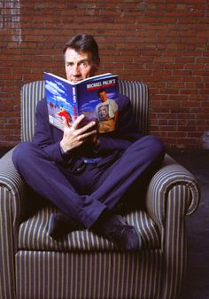 Michael Palin reading his own book while wearing a purple suit while sitting on a striped couch British Comedy, British Actors, British Men, Funny People, Funny Guys, Striped Couch, English Comedians, Nordic Wedding, Michael Palin