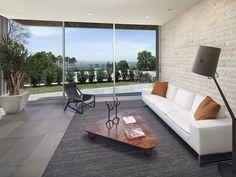 Une jolie façade de maison grâce au contraste de la baie vitrée ...