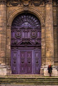 Ornate purple doors with brick walls.