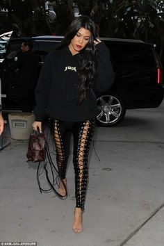 Flashing the flesh! Kourtney Kardashian stepped out in a pair of lace-up PVC trousers that clung to her legs for a night watching the Lakers take on the Cavaliers in Los Angeles on Sunday