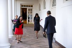 President Barack Obama watches as First Lady Michelle Obama playfully greets him on the Colonnade of the White House.