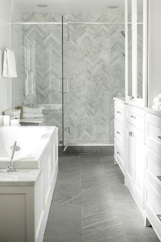 White bathroom with porcelain bathroom floor in dark grey with chevron pattern shower wall tile and glass doors
