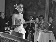 """""""Singer, Lena Horne, flower tucked behind her ear (perhaps in tribute of Billie Holiday who famously wore a gardenia in her hair)  performs at a lounge in the Savoy-Plaza Hotel in late 1942 in New York, New York."""" To the right sits Fredi Washington,  Photo: Michael Ochs"""
