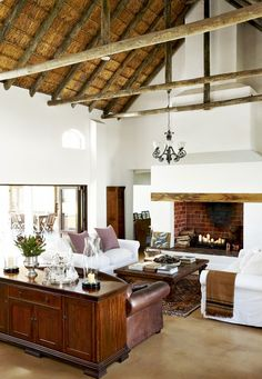 Exposed ceiling beams in living room with white walls, fireplace, and white sofa with purple pillows