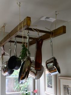 a wooden antique ladder/pot rack hanging from a ceiling is a brilliant kitchen storage solution for small apartments