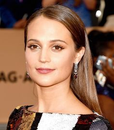 Alicia Vikander's sleek center-part, gold eyeshadow, and rose lip color are giving off major '70s vibes