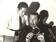 Charlie Chan and son Lee observe a clue.