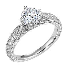 31-553-E Masterfully crafted, this engagement ring dazzles with its round center stone and prong set diamond band with delicate milgrain and beautiful engraving, filigree, kite set center, round, princess, cushion. Available at CMI Jewelry Showroom in Raleigh NC