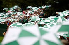 Spectators watch from under umbrellas during final round play in the 2013 Masters golf tournament at the Augusta National Golf Club in Augusta, Georgia, April 14, 2013. REUTERS/Mark Blinch