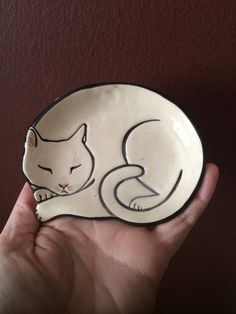 A small ceramic dish in the shape of a sleeping cat, in this case a white cat. The dish can be used as a ring dish, or to hold any type of small