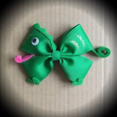 Tangled Pascal Green Disney Hair Bow. Green Grosgrain Ribbon, Goggly eye, felt coil tail and tongue, and glitter details. Mounted on an alligator clip. I can do custom bows, just let me know if youd like something specific. Price is for single bow.