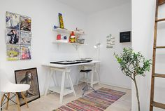 W tym aneksie biurowym w skandynawskim stylu do przechowywania służą otwarte półki na ścianie i koziołkach biurka. Te białe elementy wyposażenia dyskretnie wtapiają się w tło białej ściany. Indywidualny charakter kącika do pracy ukształtowały kolorowe dodatki – biurowe akcesoria i bibeloty, pasiasty dywan, magazyny w ściennym uchwycie.