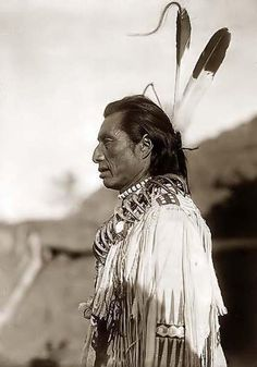 Crows Heart, an Indian Brave. It was created in 1908 by Edward S. Curtis.    The photograph presents the Indian in a half-length portrait, facing left. He is wearing a buckskin shirt, and has two eagle feathers in his hair. He has necklaces around his neck, One of the Neclaces is made of Bear Claws.