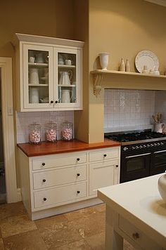 Brabourne Farm - love the fireplace mantle over the stove, glass doors on cupboards with white jugs inside, timber benchtops