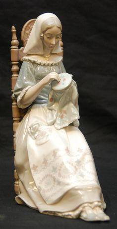 Reminds me of Snow White's mother sewing by the window.  The scene where she wished for her future daughter.  Lladro PORCELAINE .
