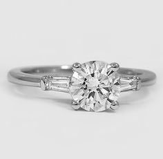 Captivating tapered baguette diamonds are bar channel-set in this elegant ring, brilliantly framing the center diamond.