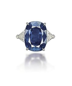 A SAPPHIRE AND DIAMOND RING, BY CHATILA  Set with a cushion-shaped sapphire, weighing approximately 22.39 carats, to the triangular-cut diamond shoulders, mounted in platinum, ring size 6, in green Chatila case Signed Chatila