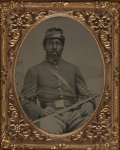 Unidentified African American soldier in Union cavalry uniform with cavalry saber in front of painted backdrop showing landscape. c. 1864