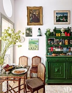 Antique Portuguese chairs are grouped with a bamboo table and a 19th-century sideboard in the kitchen's breakfast area; the portrait is English | archdigest.com