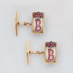 A pair of jewelled and enamelled gold cuff-links St. Petersburg, 1908-1917, unrecorded workmaster's mark A.T, with scratched inventory number 26909 Rectangular, the centre of translucent white over sunburst ground, embellished with the crowned initial 'B' set with cabochon rubies and rose-cut diamonds, marked on ring 5/8 in. (1.6 cm) long (2) - Sold for $52,061