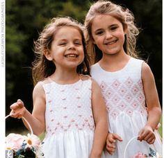 The flower girls danced down the aisle in white cotton dresses with pink smocking.