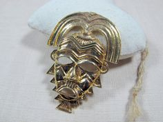 Check out this item in my Etsy shop https://www.etsy.com/listing/213894218/vintage-gold-tribal-mask-brooch