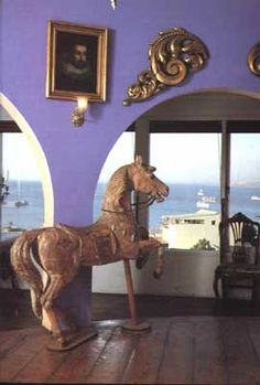 La Sebastiana living room is circular and has a merry-go-round pony placed among funny couches and clocks.