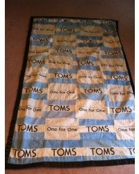 a blanket made of TOMS flags with fleece backing, I've been wanting to make one forever. Love this idea but I would do the front showing only the toms flag; the pouches with two sides would be sewn on with the pouch still accessible.