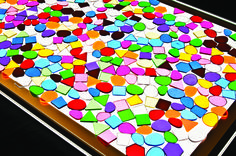 Coloured mosaic pieces on a light panel.