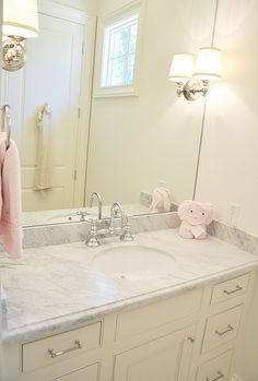 Hayden's bath - white cabinet and counter.  Large mirror and sconces.