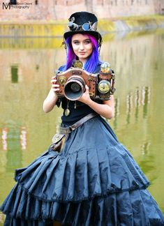 Neon Haired Steampunk Photographer (woman with pink, purple, & blue hair holding steampunk camera at Elfia 2017) - For costume tutorials, clothing guide, fashion inspiration photo gallery, calendar of Steampunk events, & more, visit SteampunkFashionGuide.com  #steampunkfashion #steampunk #fashion #elfia #costume #steampunkcostume