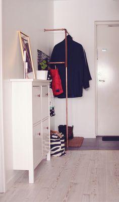 Vitt furuek golv och grått klinker. Skoskåp från Ikea med sprayade knoppar i koppar och kopparklädställning