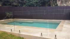 Sawn and sandblasted sandstone paving and coping tile around pool. Glass pool fence. EcoBuilt Landscaping Brisbane. Follow EcoBuilt Landscaping on Facebook.