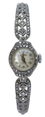 An adorable Art Deco style timepiece! The band has a subtle taper and features a pierced lattice�forming diamond shaped profiles along centre, bordered with encrusted marcasite stones. Attached at the back is a fold over clasp which attaches through a ladder style attachment - allowing for a more flexible fit. This vintage ladies wrist watch is all in working order, recently serviced and oiled with�a wind of the crown needed before wearing.