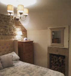 Our newly renovated cottage bedroom.  We uncovered the cotswold stone wall and repointed it. We also uncovered the fireplace which looks great stacked with logs.