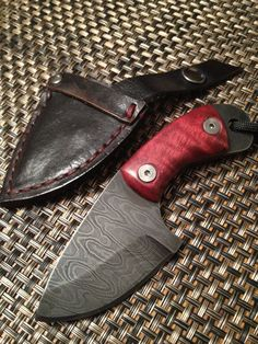 Curved back skinner knife in Damascus steel. Red stabilized curly mango handle. Black paracord with batman lanyard bead. Comes with black