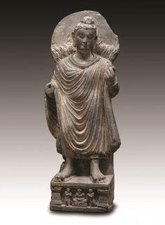 Bouddha auréolé représenté debout sur un trône orné d'un Bouddha assis en méditation entouré d'Indra et de Brahma. Ce haut-relief illustre l'épisode du «Grand Miracle de Shravastî» : Le Bouddha historique Shakyâmuni manifeste sa puissance devant l'assemblée des maîtres hérétiques en accomplissant plusieurs miracles. Il est ici représenté en lévitation au-dessus de flots s'écoulant de ses pieds et des flammes s'élèvent de ses épaules. En schiste. H : 79 cm  Art gréco-bouddhique du Gandhara…