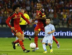 Optical illusion: Belgian's Marouane Fellaini and Vincent Kompany tower over France's Mathieu Valbuena
