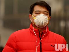 A man wears a protective face mask outside as serious heavy pollution hit Beijing on December 20, 2016. A thick layer of deep gray smog…